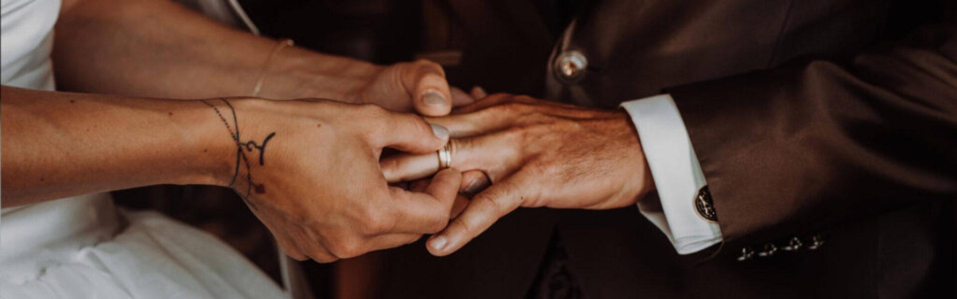 Detailbild eines Hochzeitspaares. Die Braut steckt den Hochzeitsring auf den Ringfinger des Bräutigams.