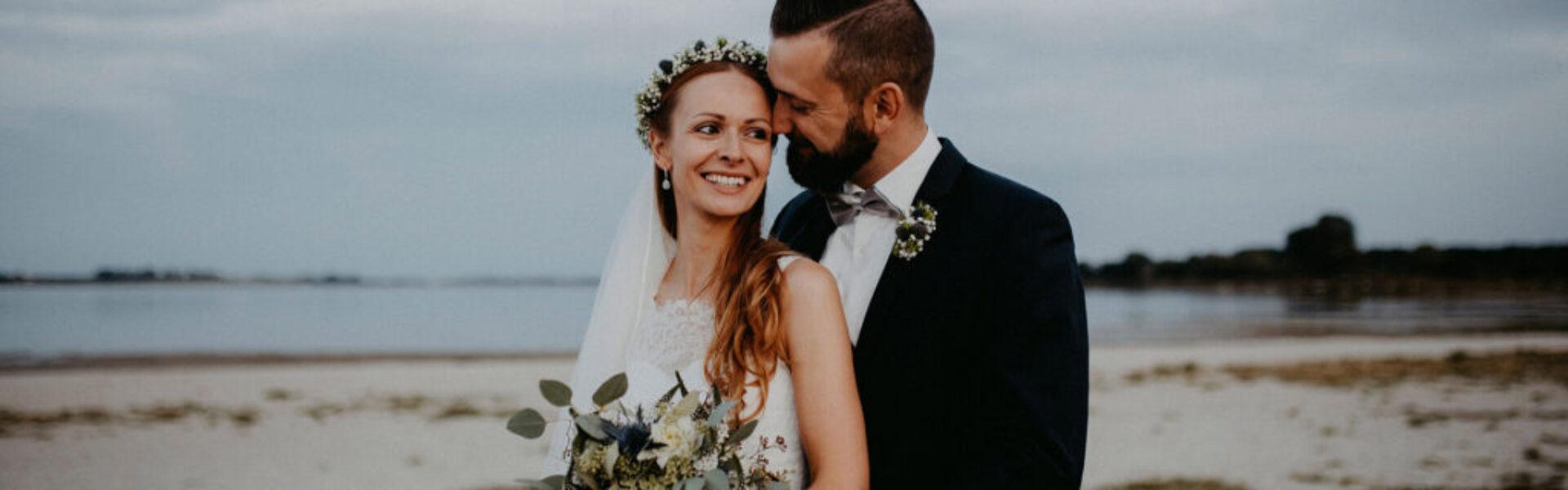Hochzeitspaar am Strand. Der Bräutigam steht hinter der Braut und beide Strahlen vor Freude