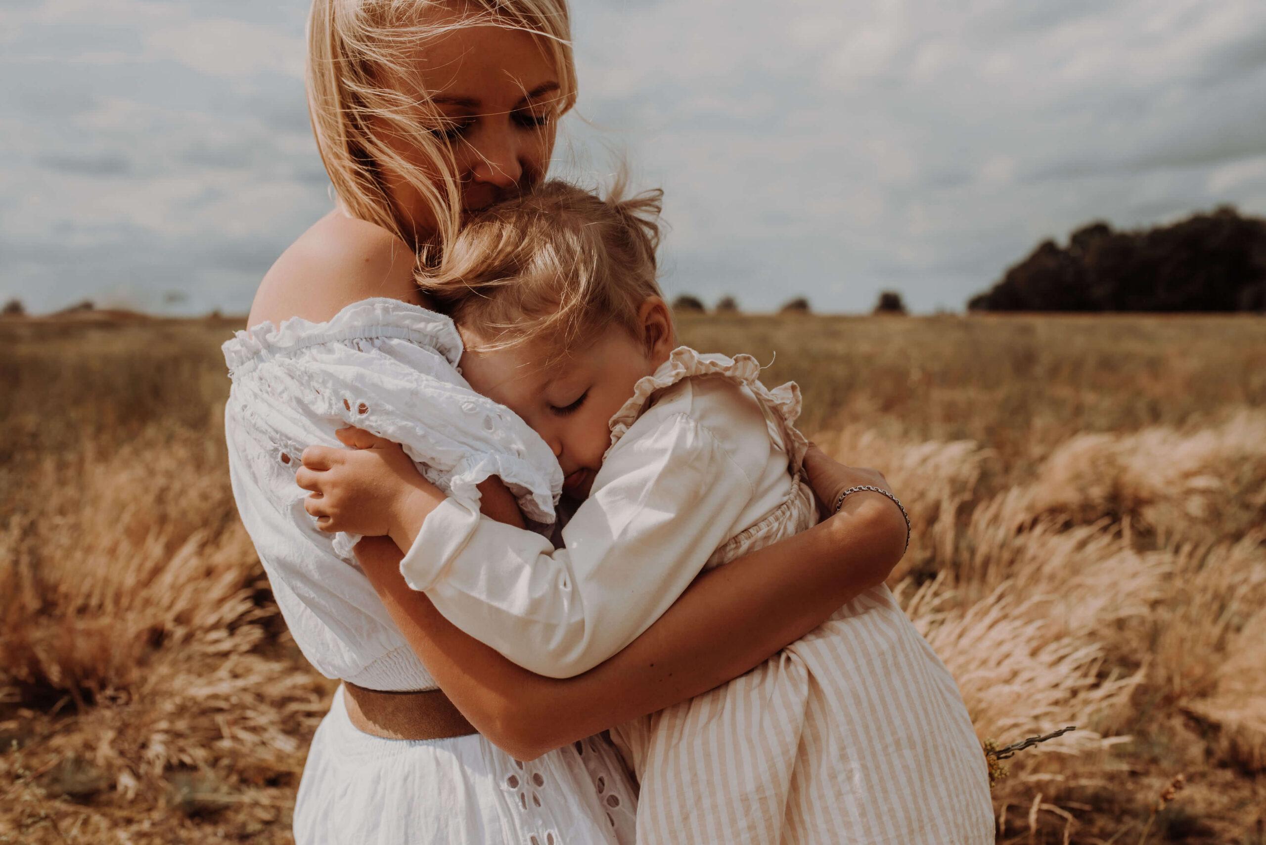 Mutter und Tochter liegen sich auf einem Feld in den Armen und kuscheln