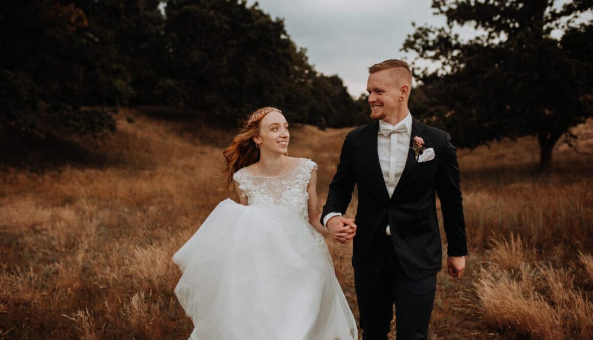 Hochzeitspaar im Wald gehen nebeneinander und schauen sich glücklich an.