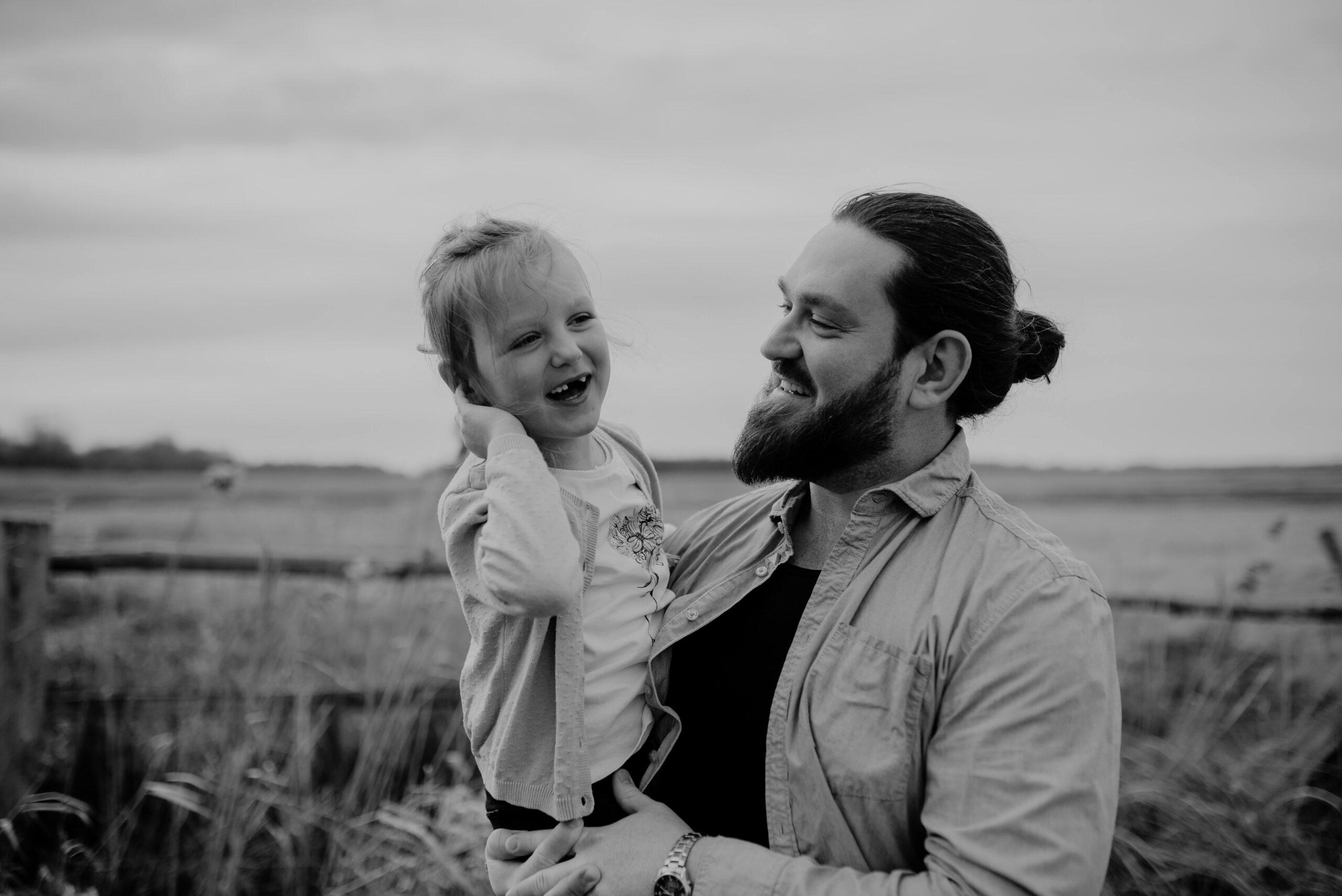 Vater und Tochter lachen in der Natur