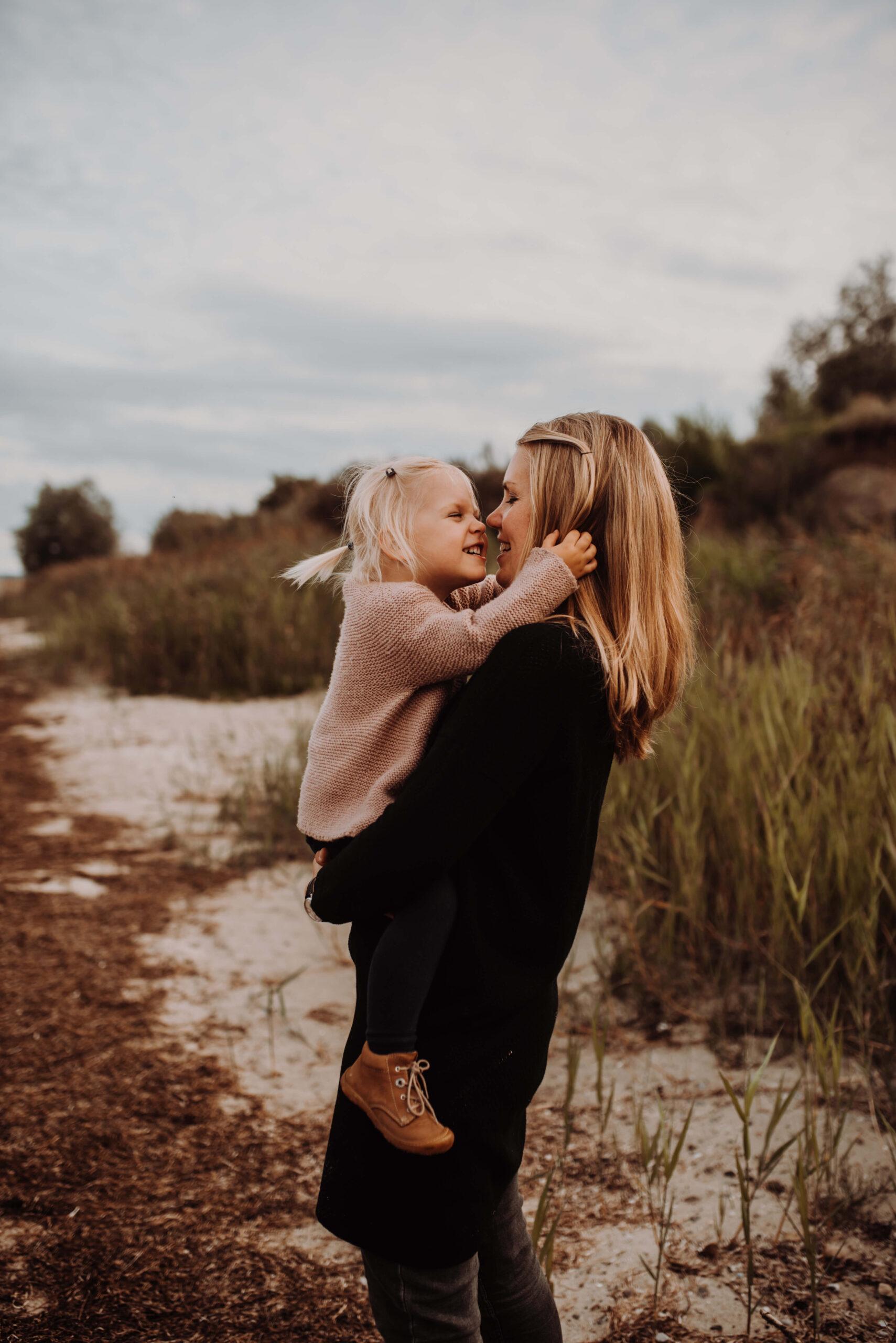 Mutter hält Tochter in der Natur auf dem Arm Sie kuscheln Nase an Nase