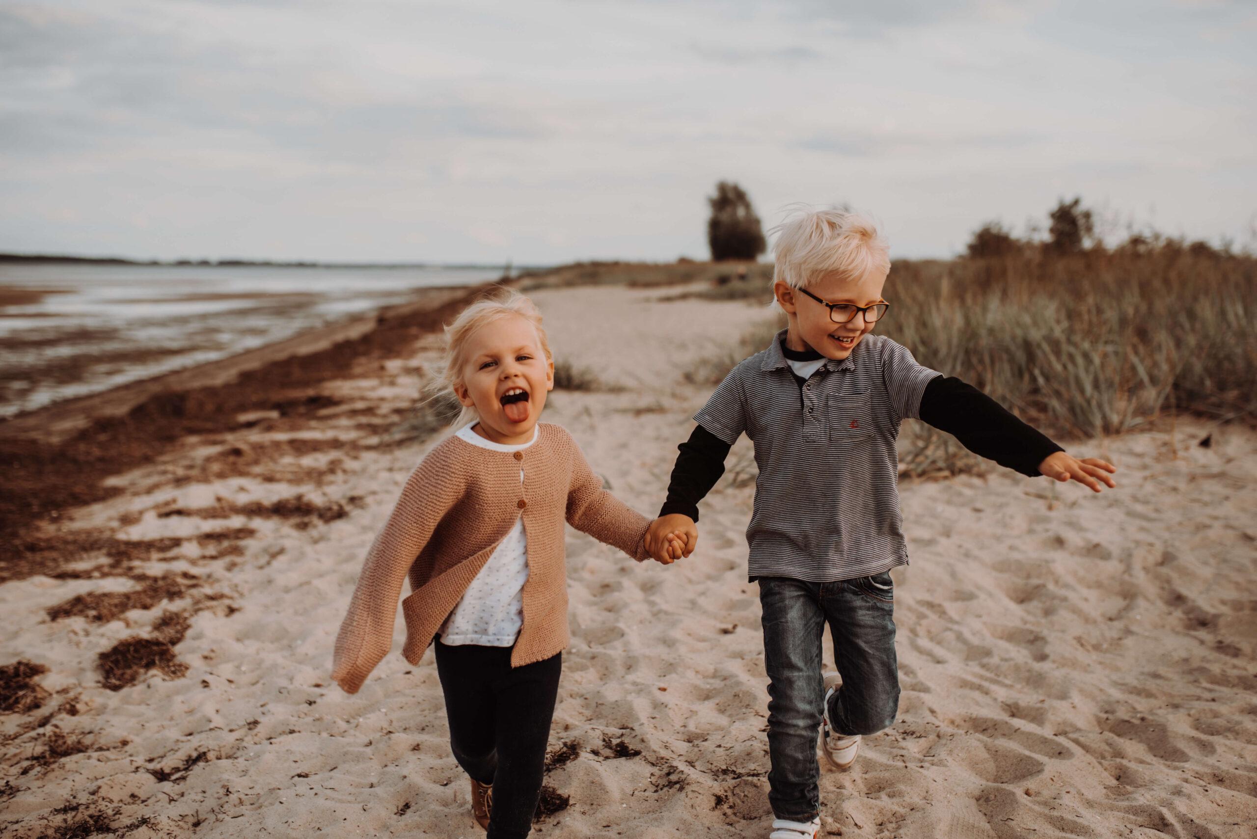 Junge und Mädchen laufen den Strand entlang
