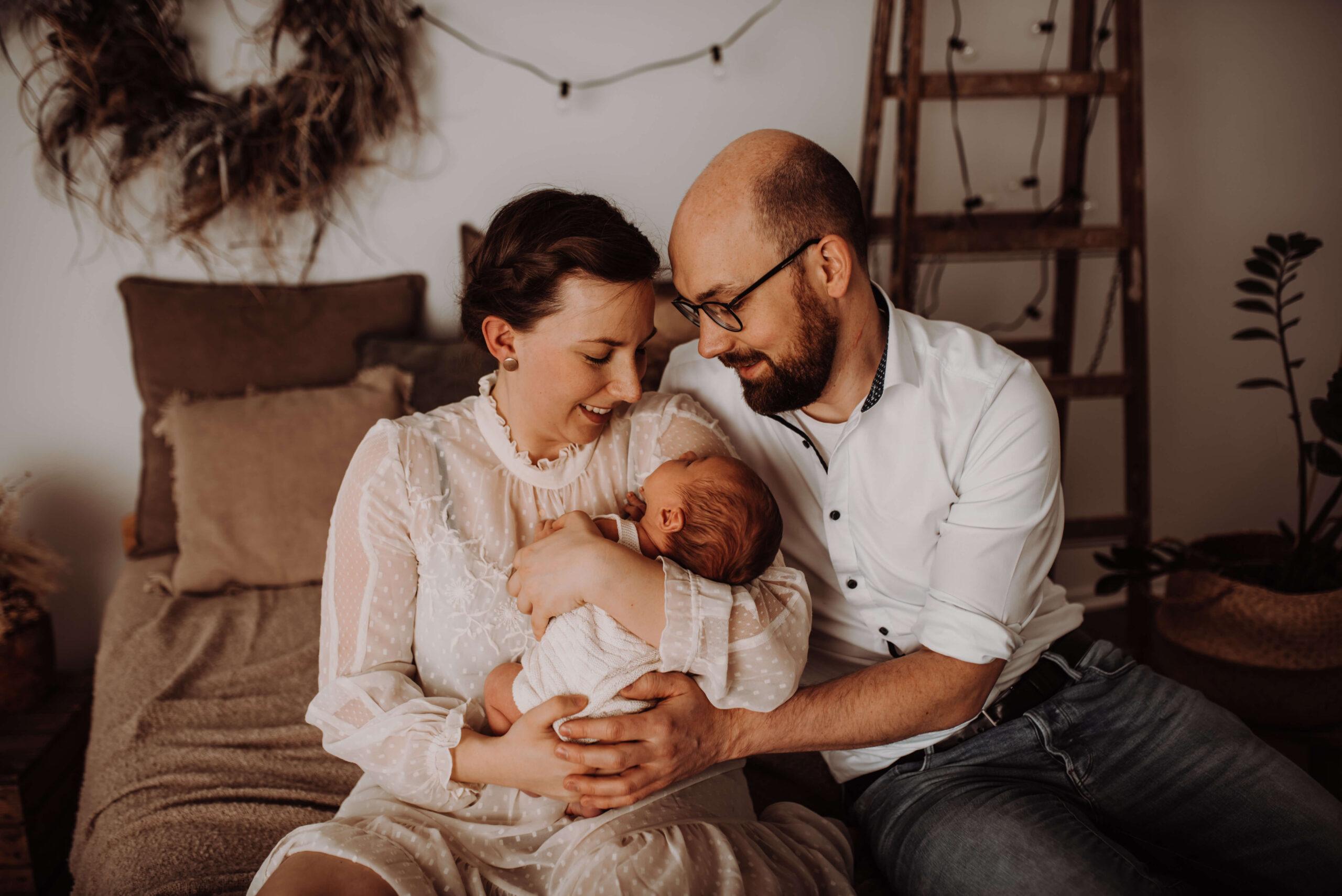Mutter und Vater halten stolz Baby im Arm, sitzen auf Bett im Fotostudio