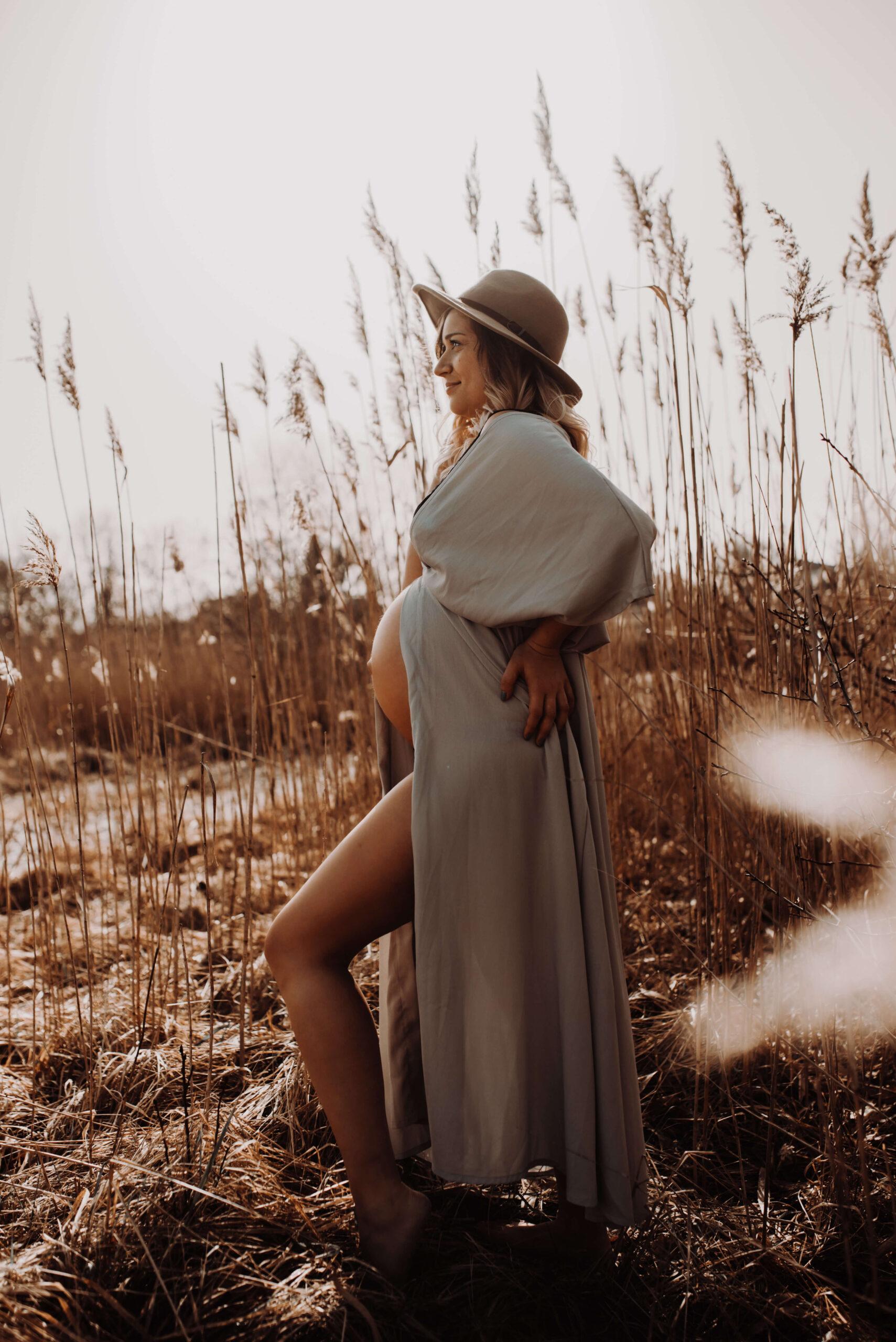 Schwangere Frau steht im hohen Gras